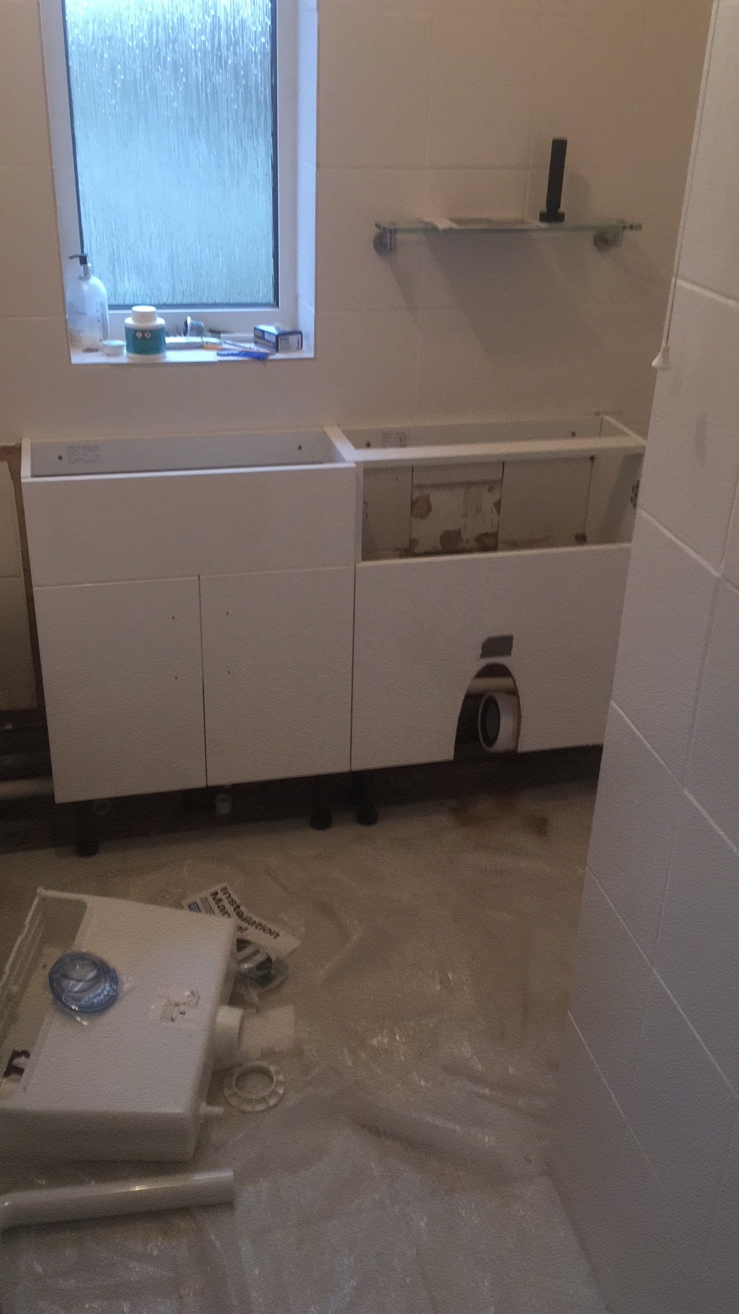 Bathroom sink and toilet partially fitted.