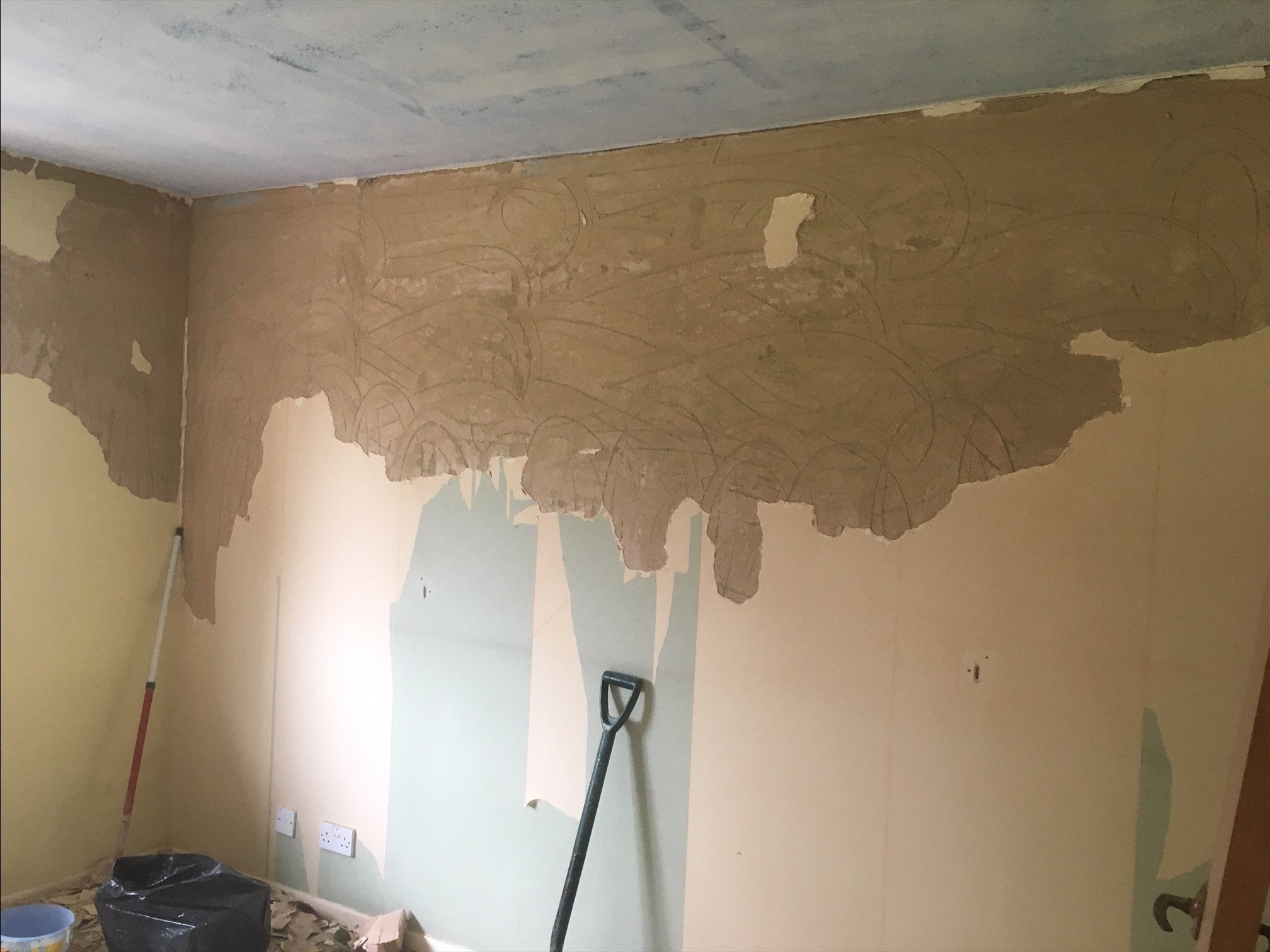 Partially plastered wall with some tools visible on the floor.
